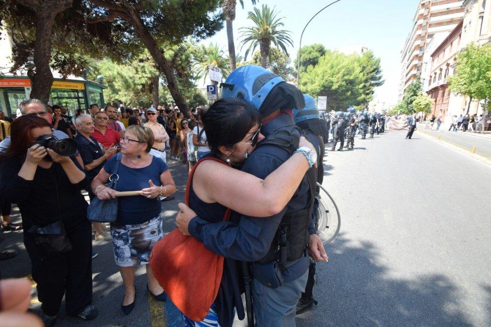"""Taranto il web si commuove per l'abbraccio tra la manifestante e l'agente, il poliziotto racconta: """"piangevo perchè sono un miracolato, sono guarito da un tumore"""""""