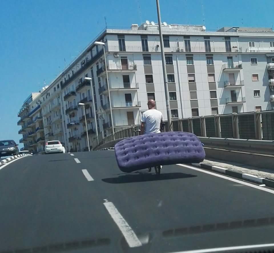 Bari, ponte di via di Vagno foto choc, uomo in bici trasporta un enorme materasso blu, la foto diventa virale