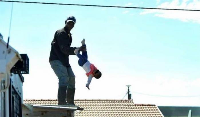 Sale sul tetto di una casa per protesta e fa dondolare nel vuoto la sua bambina, poi la lancia