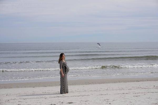 Scatta una foto in spiaggia alla moglie in dolce attesa, i due riguardano la foto e restano impressionati dalla presenza all'orizzonte